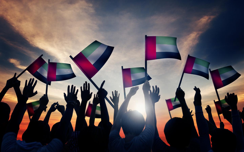 People waving UAE flags