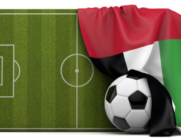 A football and football field wrapped around in a UAE flag
