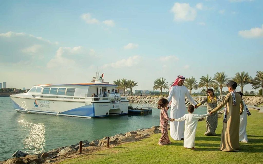 UAE family playing next to a lake