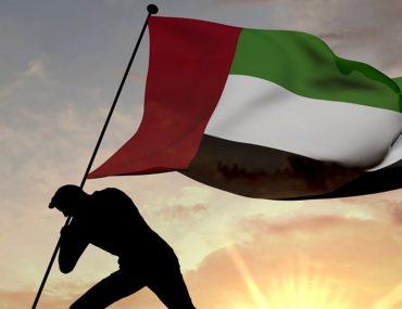 Man raising UAE flag in the desert