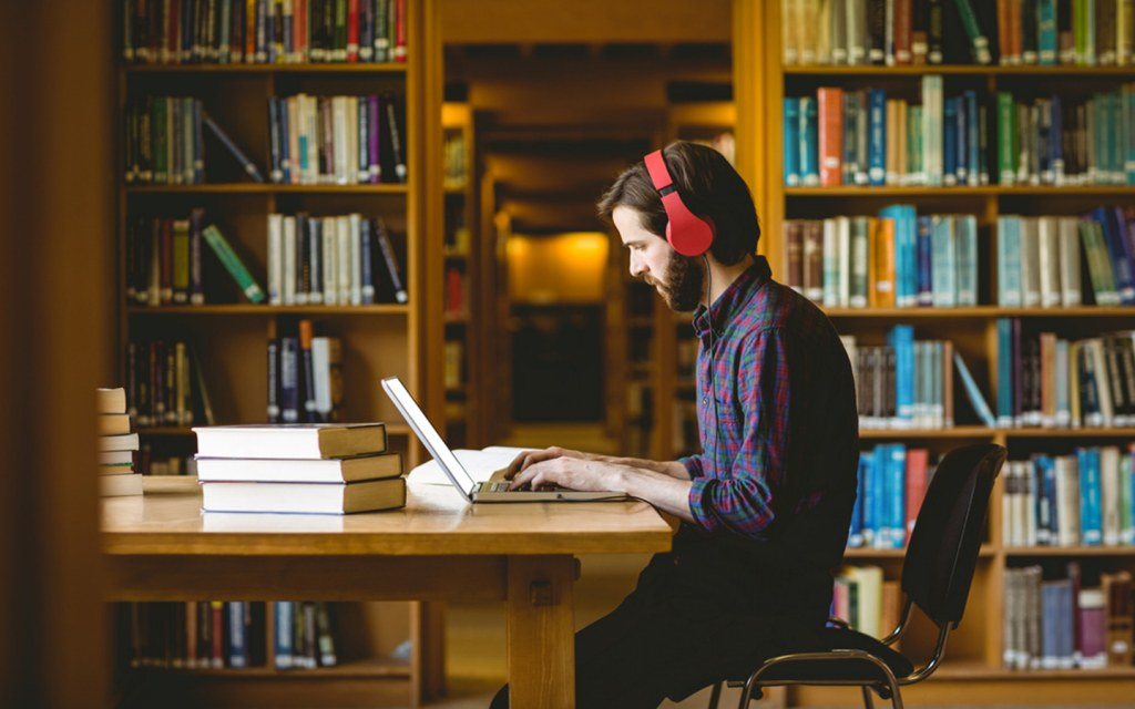 A man making assignment at a library in a university