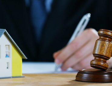 Person signing a usufruct property contract with a model house and a gavel in front