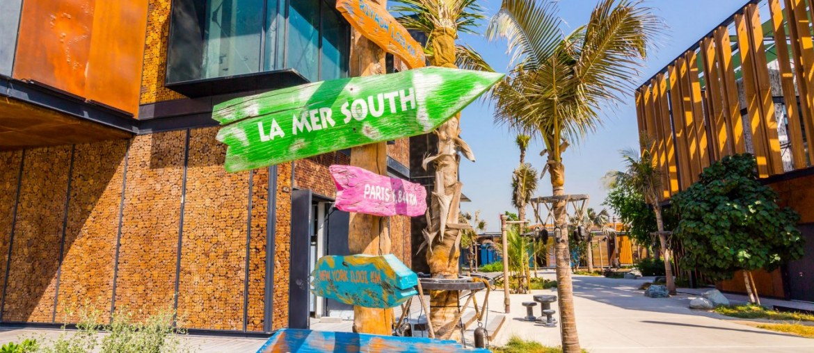 A colourful road sign at La Mer Dubai showing directions to La Mer South and other areas of La Mer, with restaurants and palm trees in the background