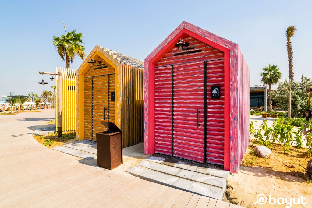 Two colourful and quirky indoor showers at La Mer Beach with blue skies and palm trees in the background