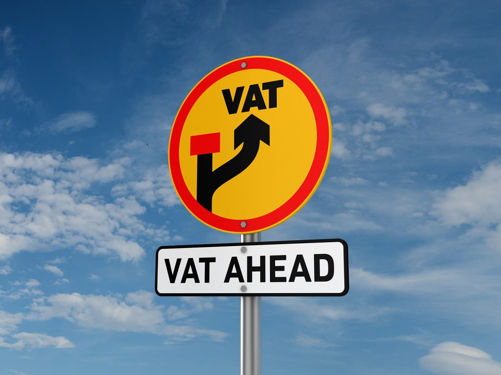 A road sign with the words VAT AHEAD written on it against a blue sky