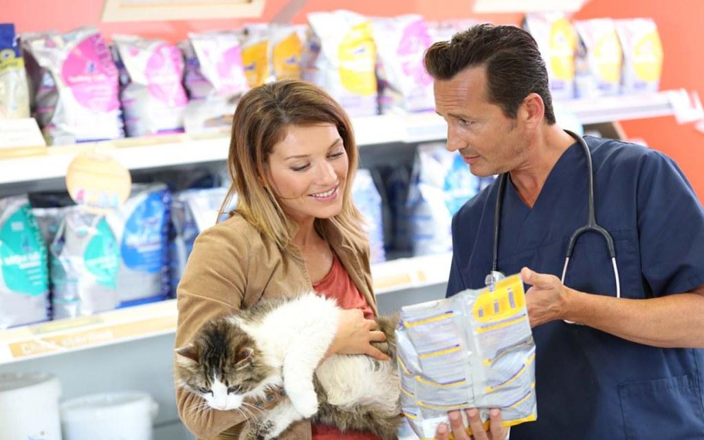 طبيب وإمرأة مع قطتها في متجر طعام الحيوانات