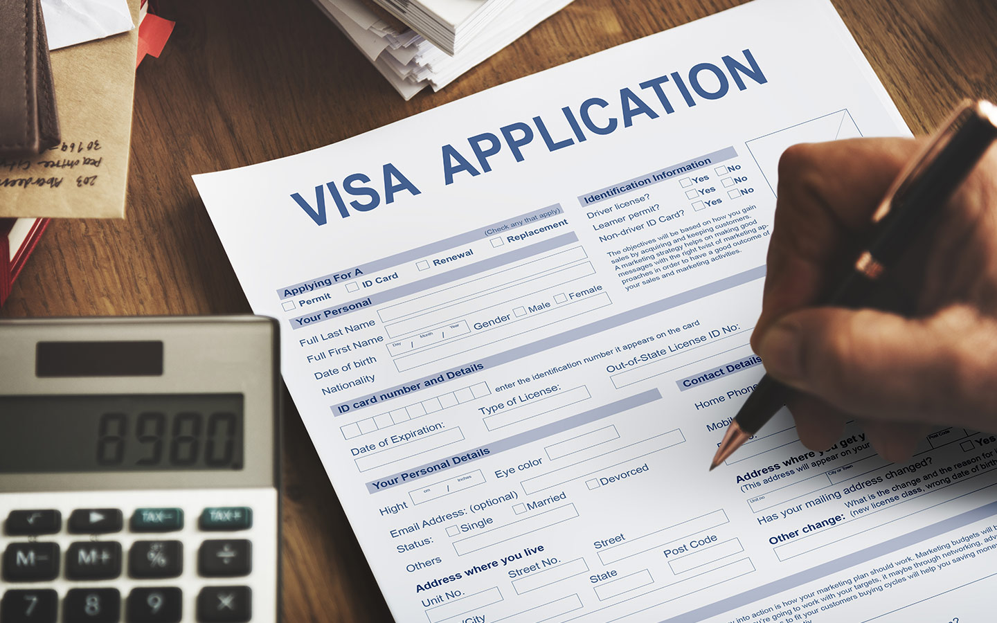 Investor visa application form with passport and phone beside it