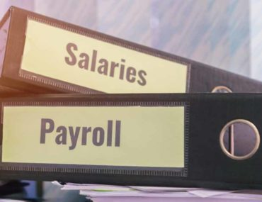 Salaries and payroll folders on a desk for WPS in the UAE