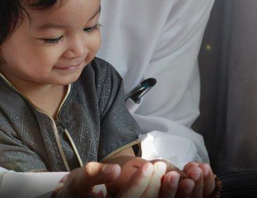 Small boy with prayer cap praying on a man's lap