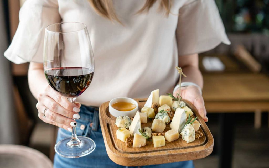 woman with a glass of wine and a cheese platter
