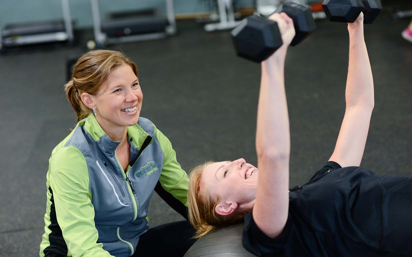 A woman exercises under the guidance of a woman coach