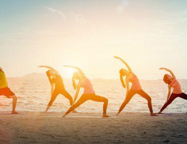 people doing yoga on the beach