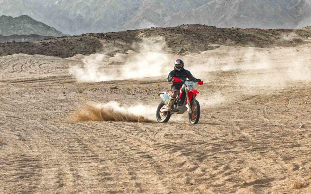 Off road biker wearing helmet driving in desert