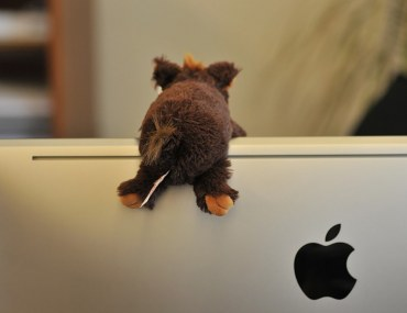 A tiny plush toy is climbing over an Apple Computer monitor in a cozy home; article on Apple TV 4K by Bayut