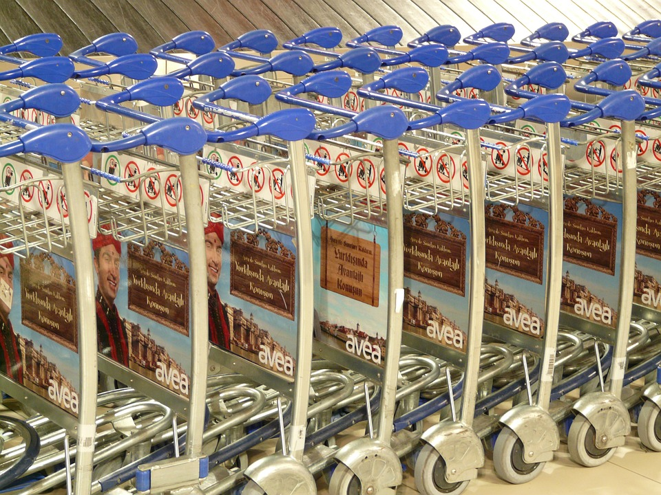 A long stack of identical shopping carts in a supermarket