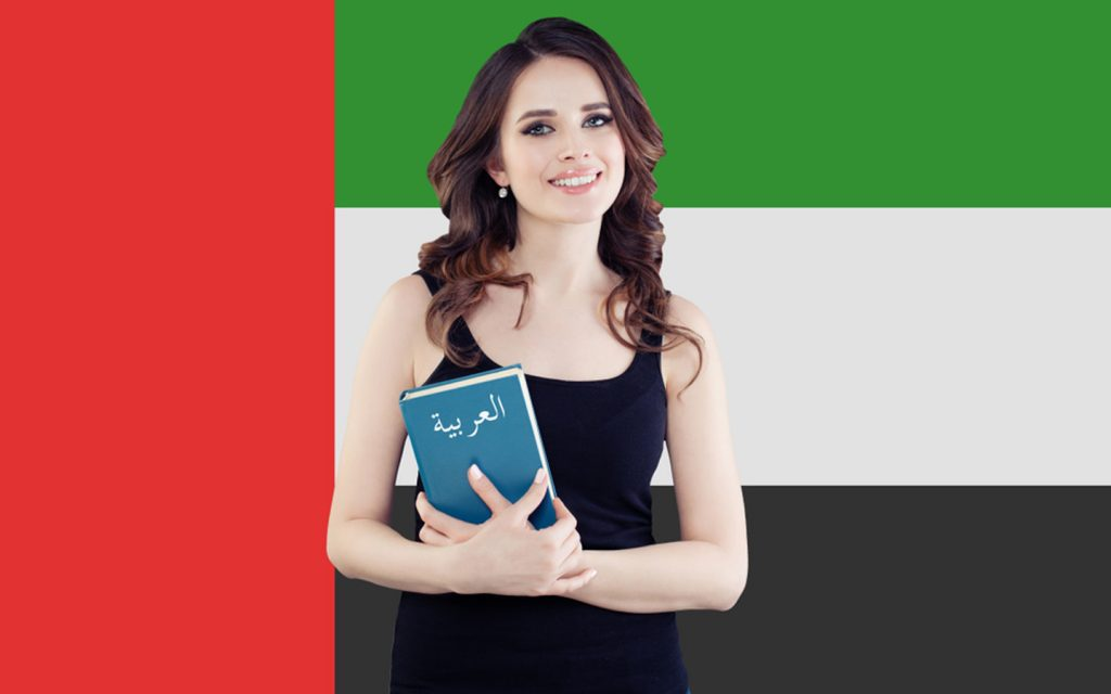 Woman holding Arabic instruction guide with the UAE flag in the background