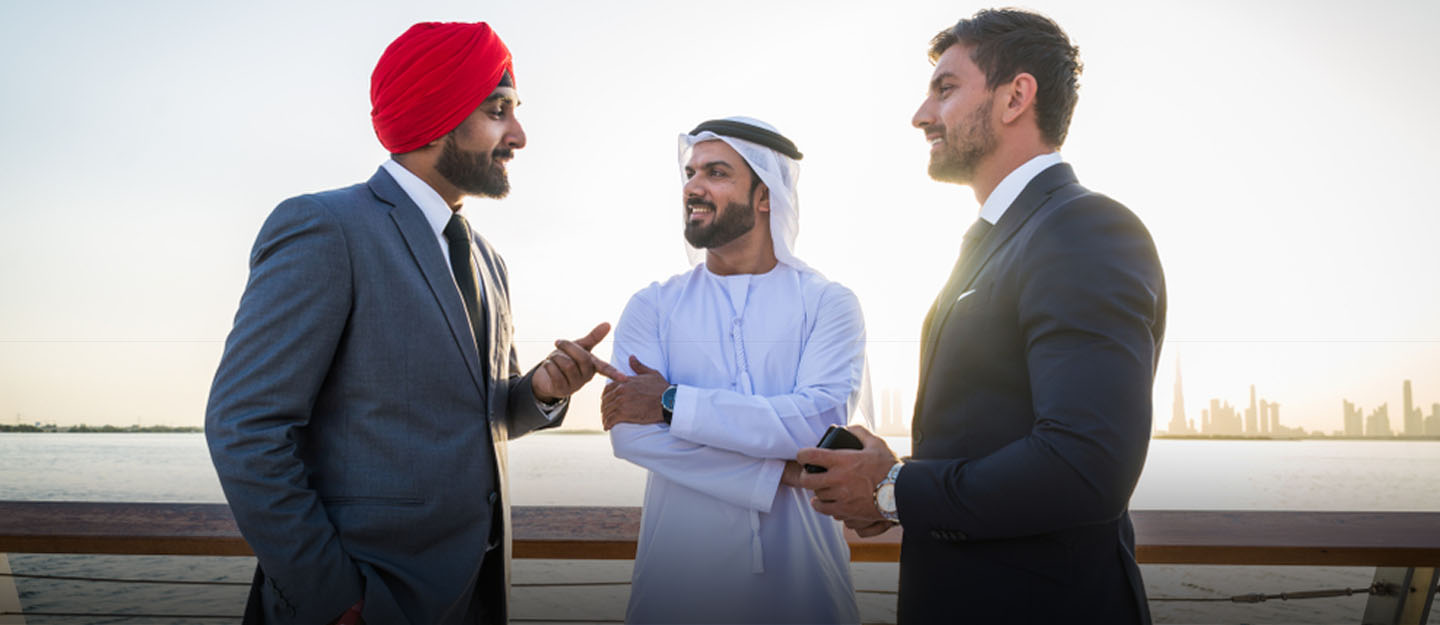 Foreign workers in business suits talking to Emirati