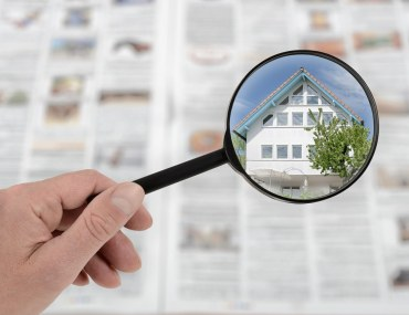 a hand holding a magnifying glass over a newspaper and magnifying a beautiful villa
