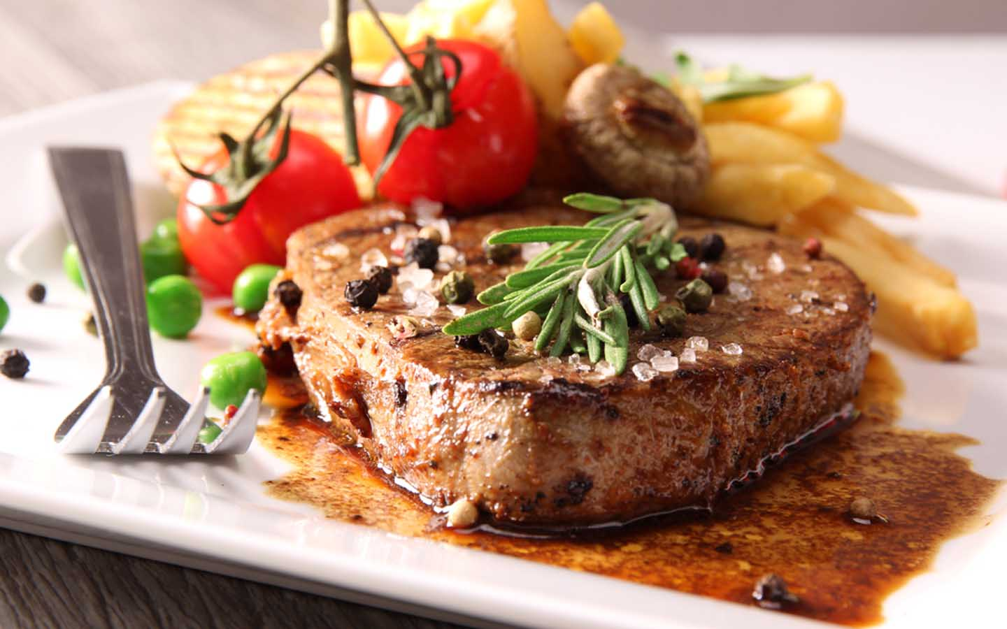 Grilled beef steak on a bed of sauce