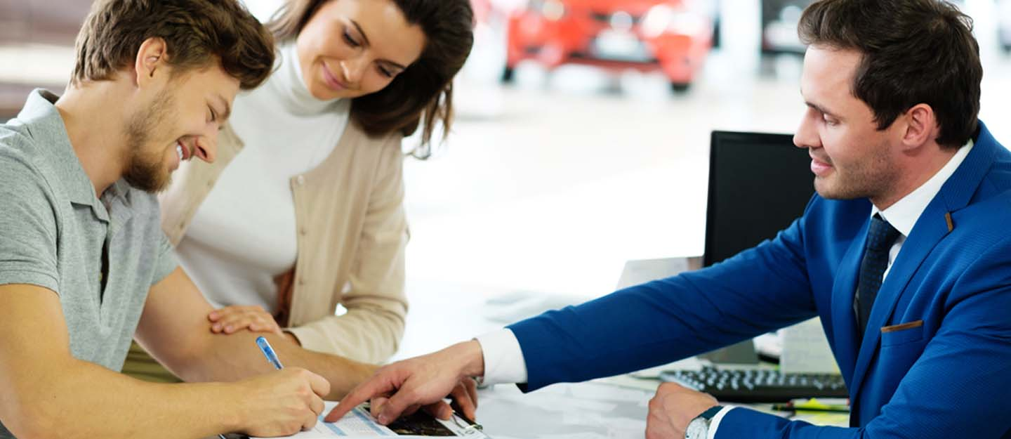 Couple signing documents before buying a car