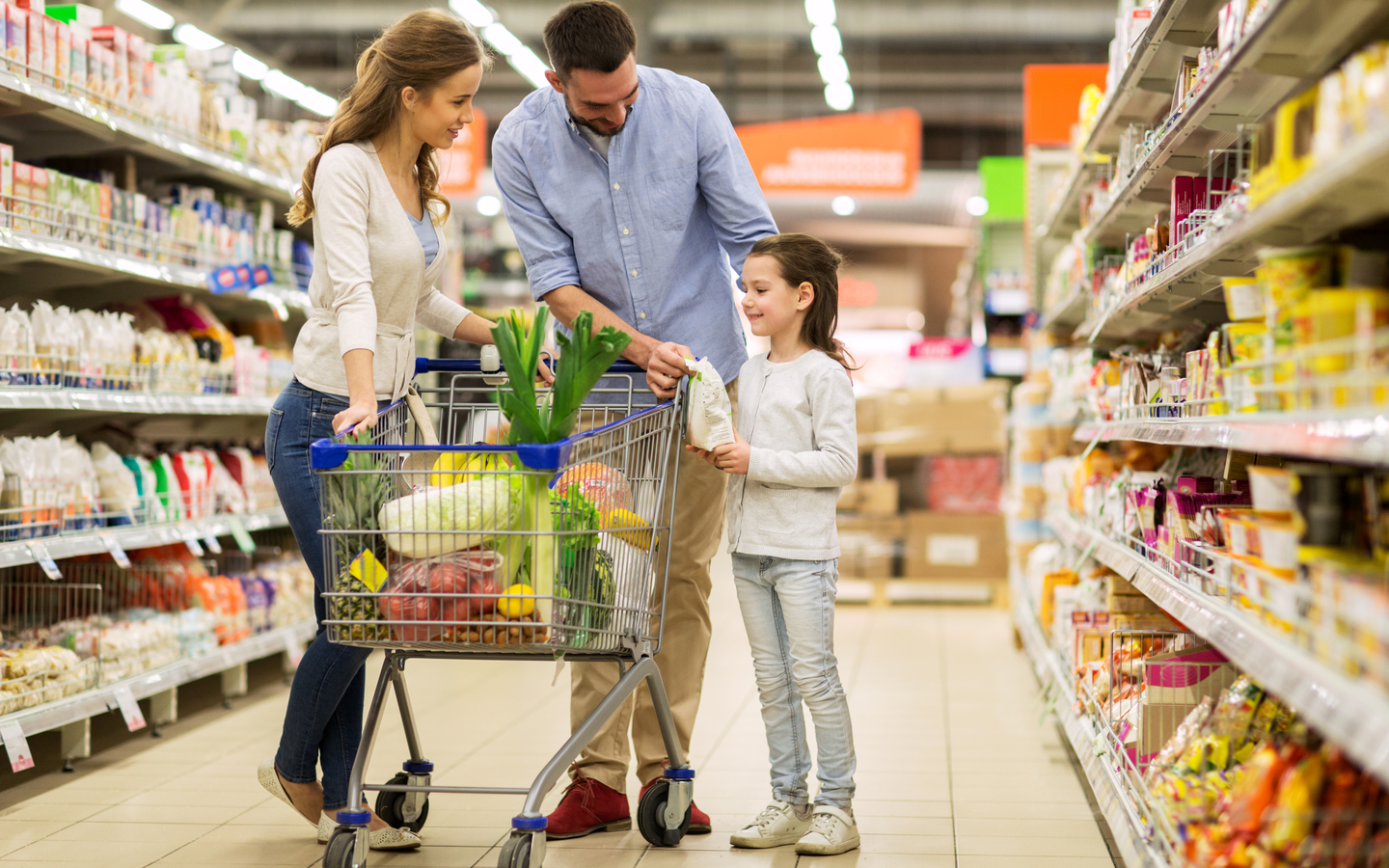 A family purchasing everyday essentials at a supermarket