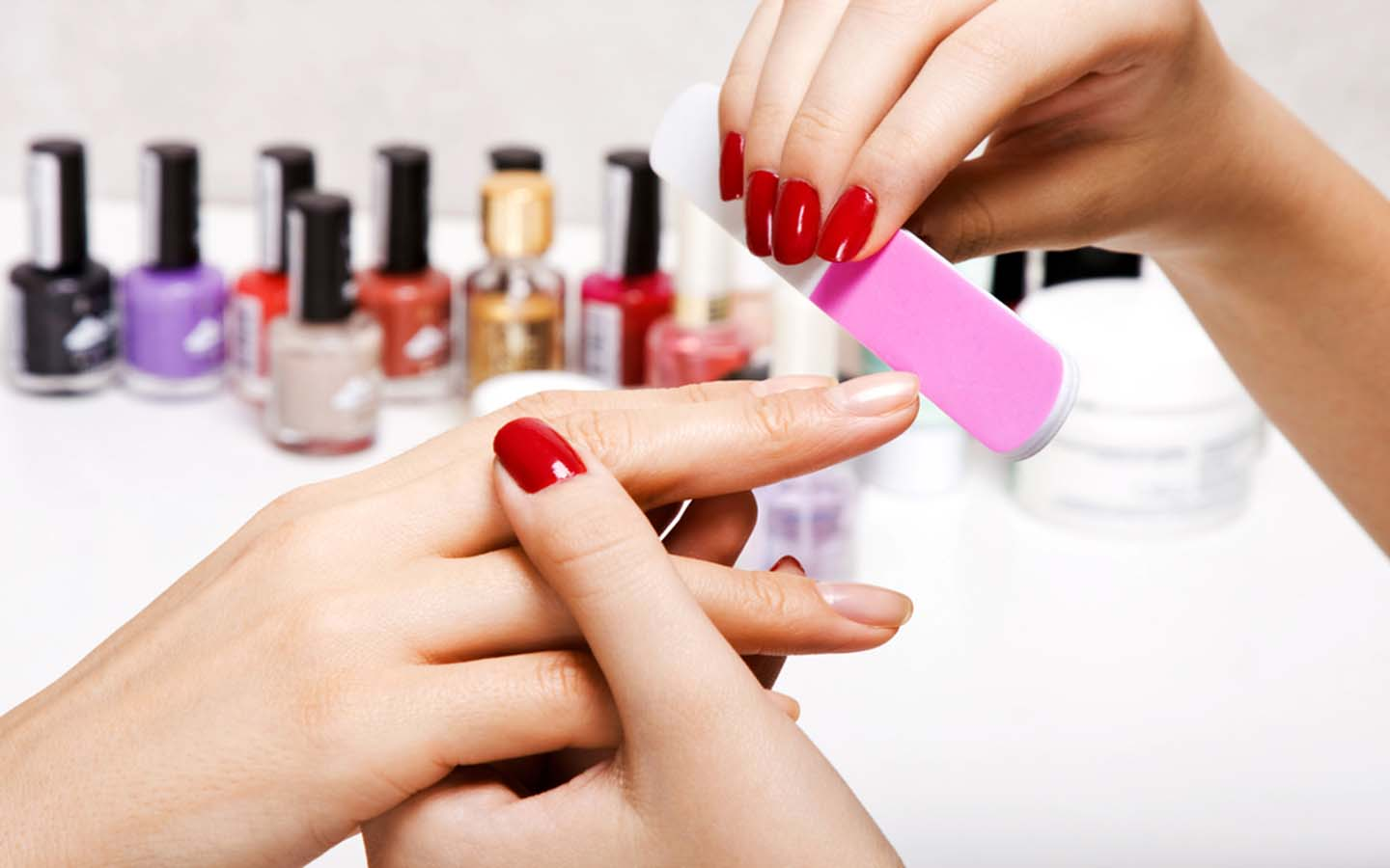 A beautician is doing manicure of the client
