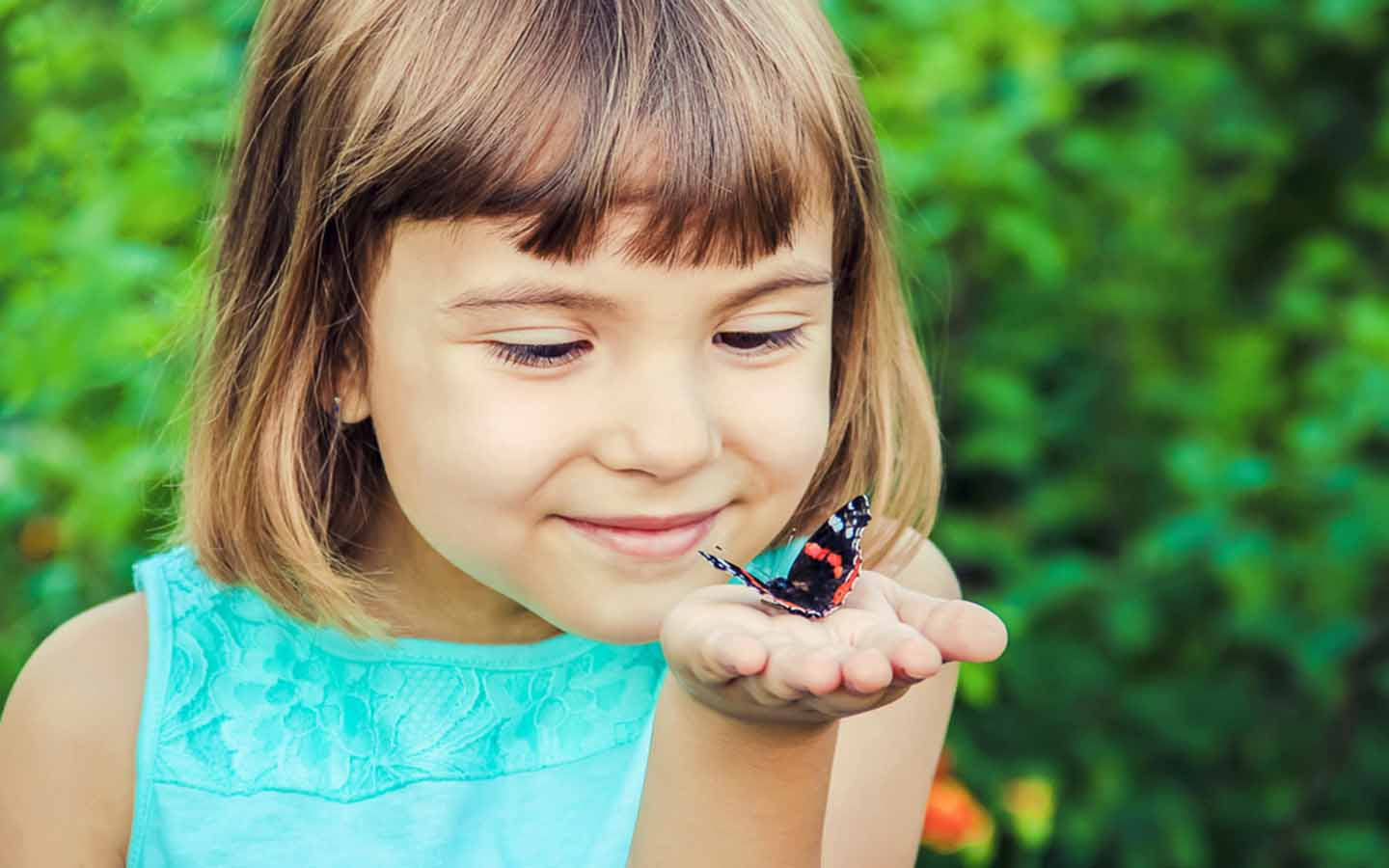 child with butterfly on hand