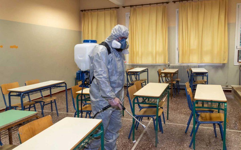 عامل يرش مدرسة