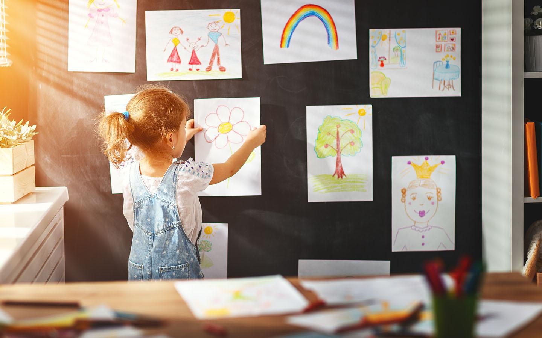طفلة تضع الرسومات على حائط غرفتها