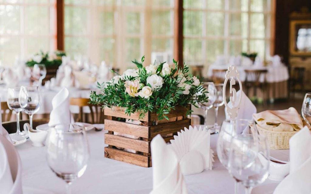 طاولة مزينة بأزهار بيضاء مع داخل علبة خشبية