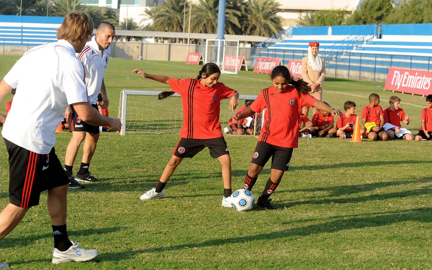 Girls playing football under the surveillance of a coach