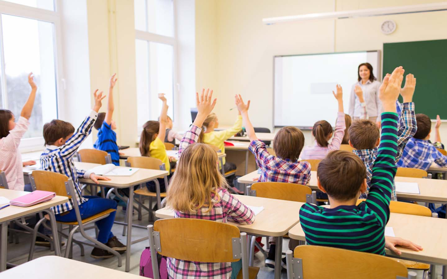 Children raising their hands to answer a question in class