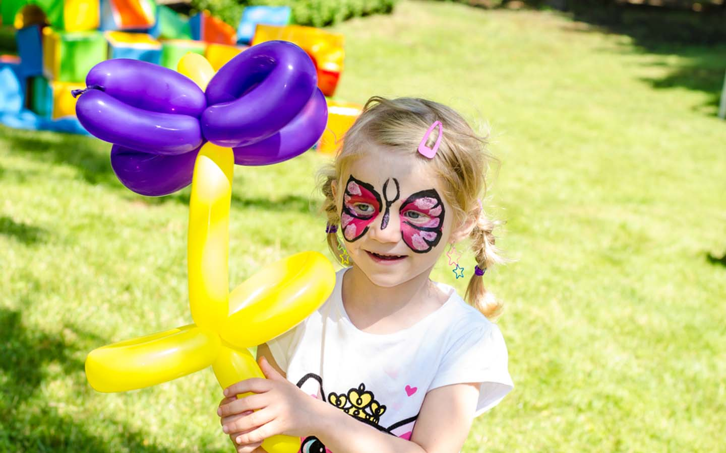 Girl with face paint holding balloon