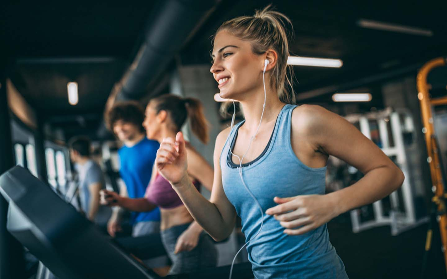 Women are running simultaneously on different treadmills at the gym