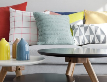 Colorful pillows on a sofa with little vase in foreground.