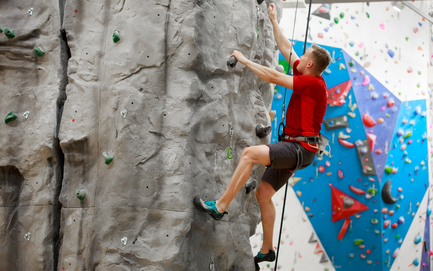 Man in a harness doing rock climbing in an indoor facility