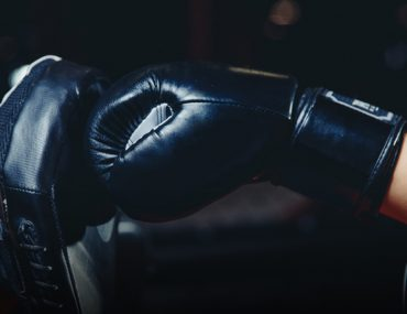 shot of gloved hand punching bag