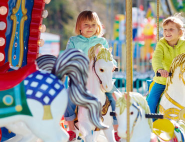 أطفال يلعبون بالأحصنة الدوارة