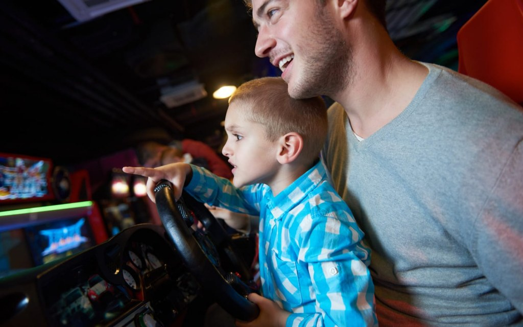 Kid playing arcade with his father