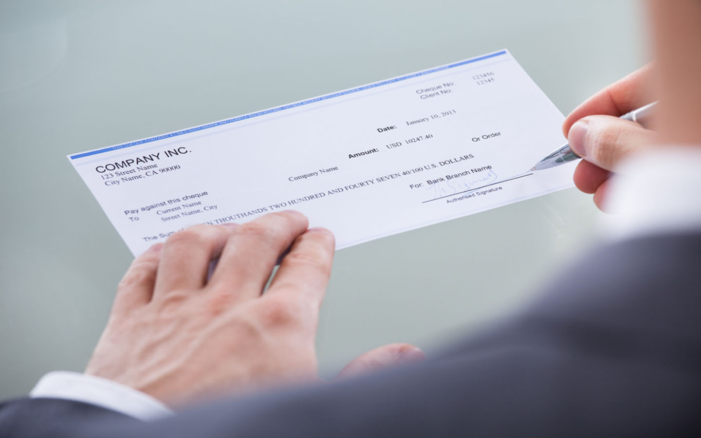 man signing cheque