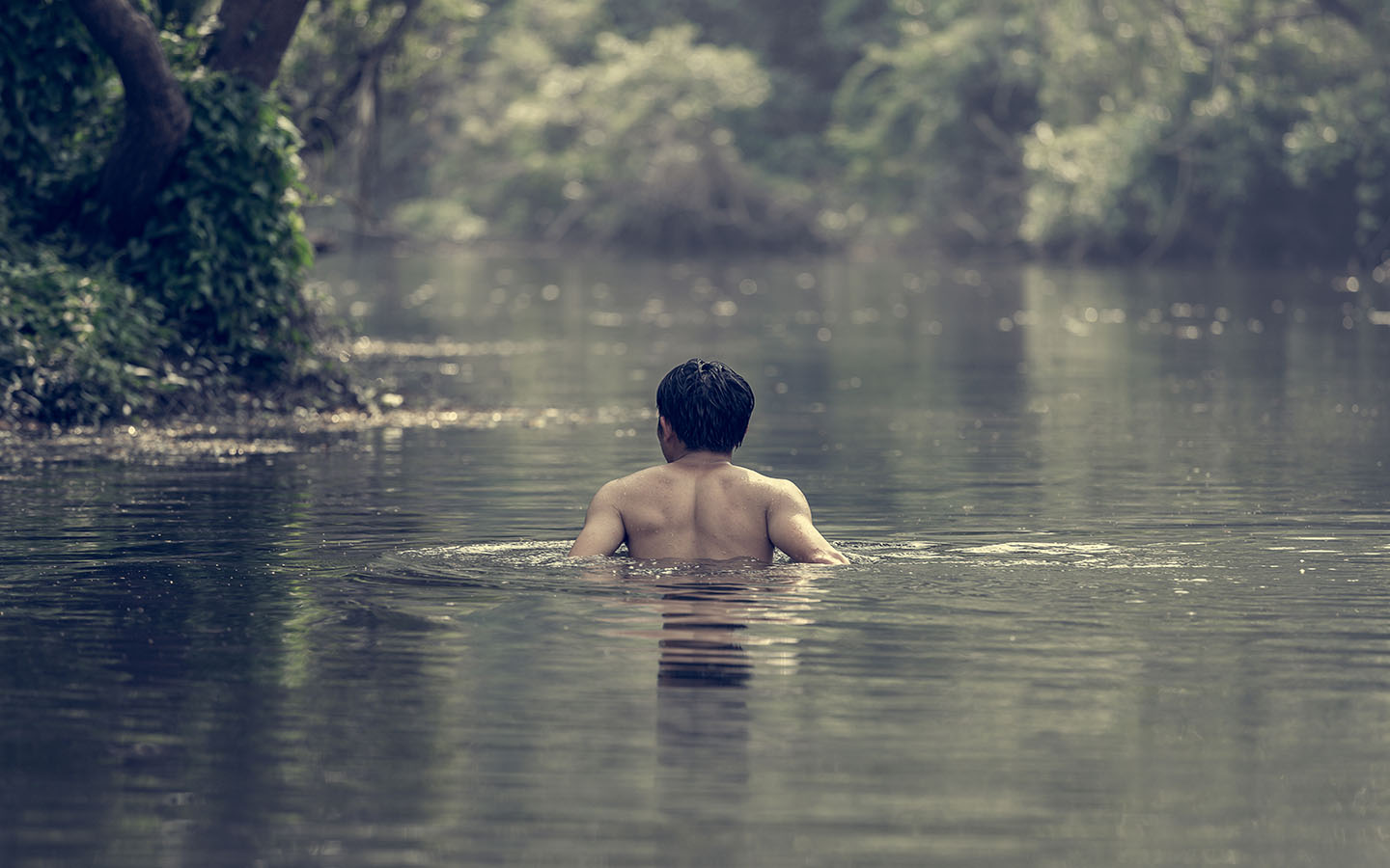 man bathing in a natural pool