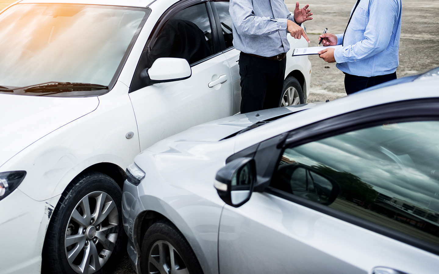 Two people standing by cars in an accident
