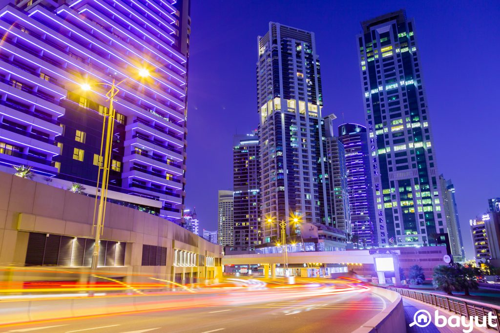 Dubai Marina at night with blue hues of the sky and buildings contrasted with the yellows of the street lights and cars on the street in long exposition