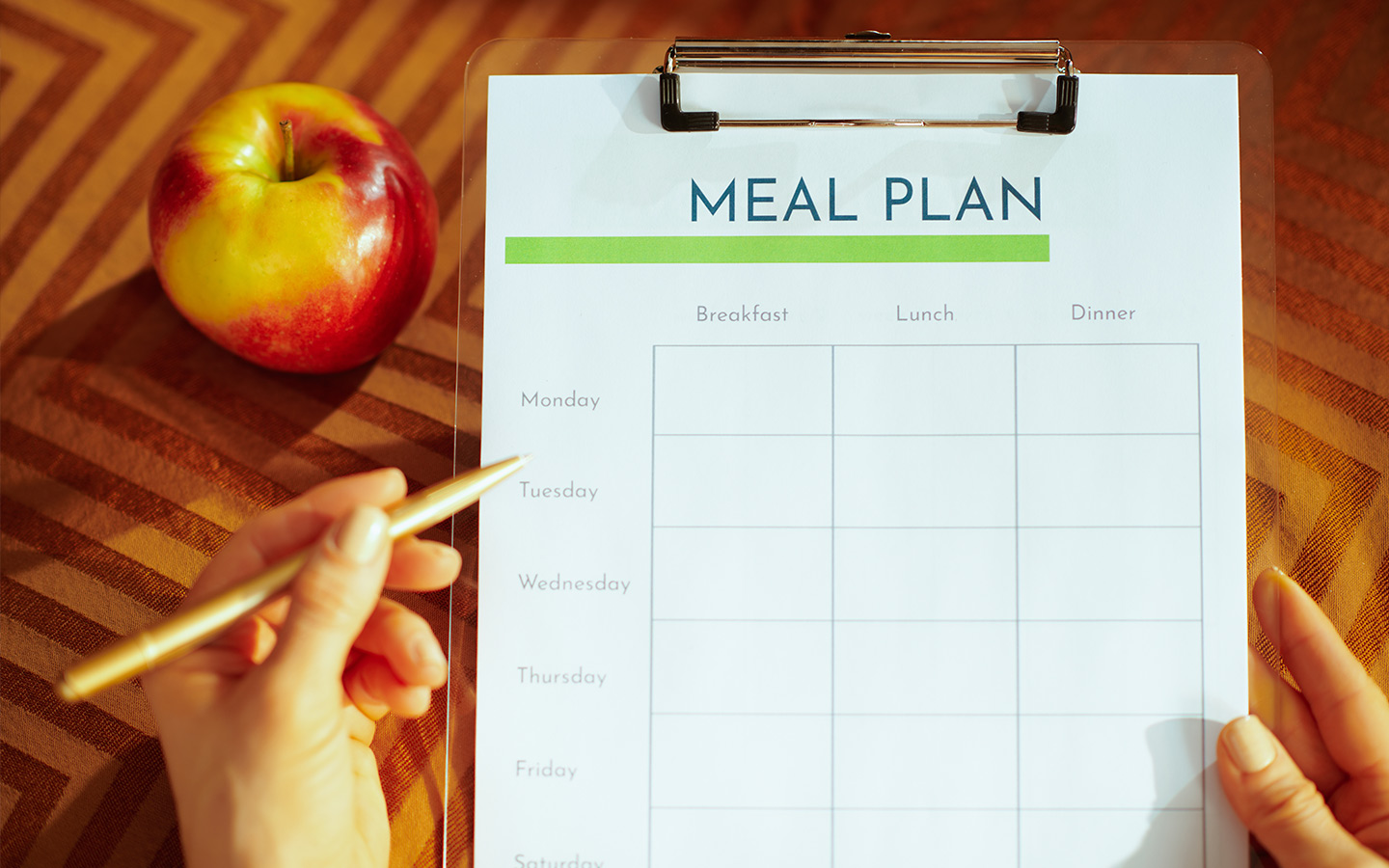 Paperclip board with meal plan sheet on it