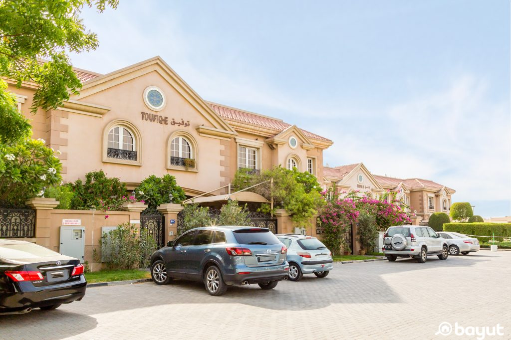 A beautiful house in Midriff area Dubai with plenty of trees and landscaping and a group of cars parked outside on a bright sunny day