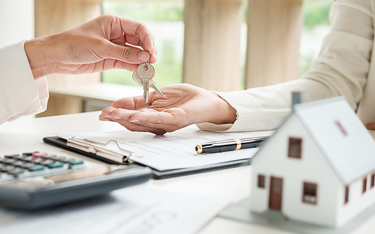 Real estate agent handing a key to the buyer