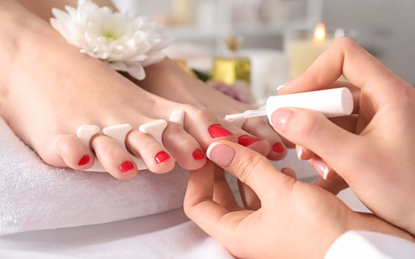 A girl is applying nail polish on the toe nails of a lady