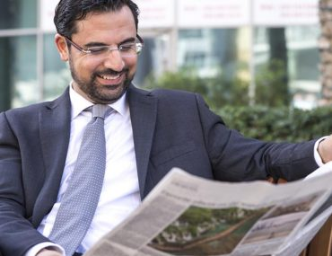 Man reading newspaper in Dubai