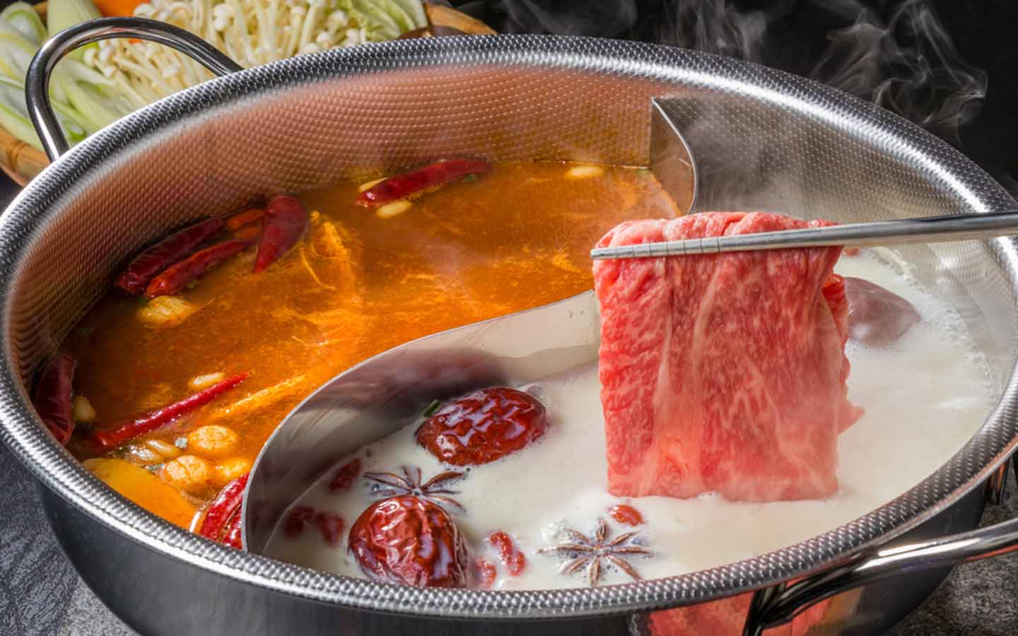 Chinese hot pot being prepared with herbs