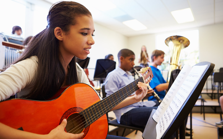 A young girl playing a guitar at a guitar class